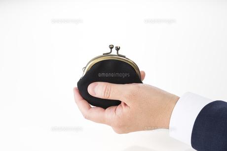 がま口財布を持ったビジネスマンの手の写真素材 [FYI04838672]