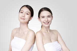 白いオフショルダーのトップスを着て並ぶコーカサス人とアジア人の若い女性の写真素材 [FYI04839201]