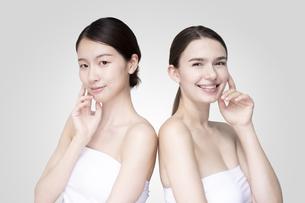 白いオフショルダーのトップスを着て並ぶコーカサス人とアジア人の若い女性の写真素材 [FYI04839203]