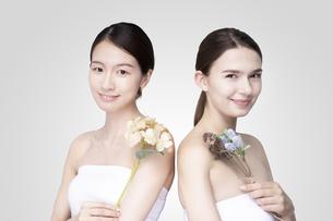 白いオフショルダーのトップスを着て並ぶコーカサス人とアジア人の若い女性の写真素材 [FYI04839205]