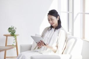 ソファに座りタブレット端末を見る女性の写真素材 [FYI04839432]