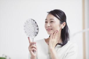 鏡を見ながらスキンケアをする女性の写真素材 [FYI04839434]