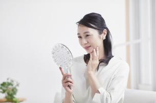 鏡を見ながらスキンケアをする女性の写真素材 [FYI04839437]
