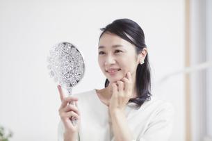 鏡を見ながらスキンケアをする女性の写真素材 [FYI04839439]