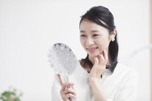 鏡を見ながらスキンケアをする女性の写真素材 [FYI04839441]