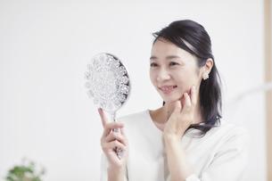 鏡を見ながらスキンケアをする女性の写真素材 [FYI04839444]