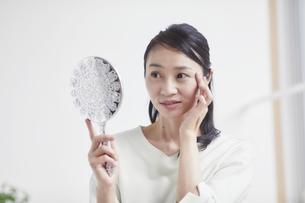 鏡を見ながらスキンケアをする女性の写真素材 [FYI04839446]