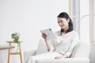 ソファに座りタブレット端末を見る女性の写真素材 [FYI04839447]