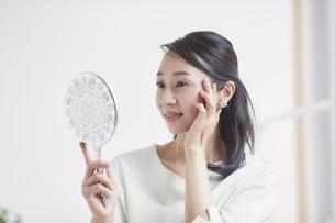 鏡を見ながらスキンケアをする女性の写真素材 [FYI04839449]