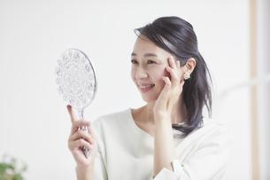 鏡を見ながらスキンケアをする女性の写真素材 [FYI04839452]