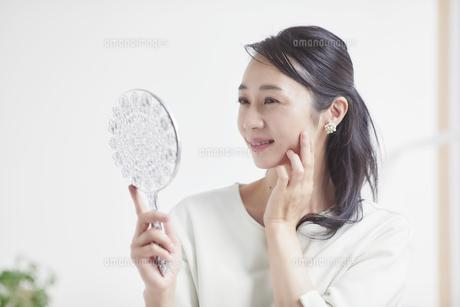 鏡を見ながらスキンケアをする女性の写真素材 [FYI04839455]