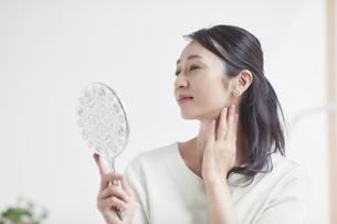 鏡を見ながらスキンケアをする女性の写真素材 [FYI04839459]