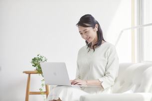 ソファに座りパソコンを見る女性の写真素材 [FYI04839461]