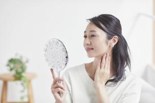 鏡を見ながらスキンケアをする女性の写真素材 [FYI04839463]