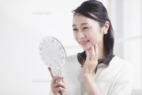 鏡を見ながらスキンケアをする女性の写真素材 [FYI04839474]