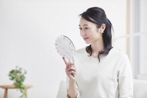 鏡を見ながらスキンケアをする女性の写真素材 [FYI04839477]