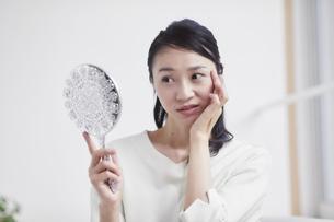 鏡を見ながらスキンケアをする女性の写真素材 [FYI04839482]