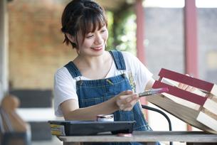 箱に刷毛でペンキを塗っている女性の写真素材 [FYI04839483]