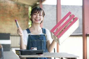 刷毛と手作りの箱を持って笑っている女性の写真素材 [FYI04839488]
