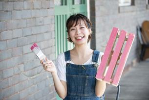 刷毛と手作りの箱を持って笑っている女性の写真素材 [FYI04839492]