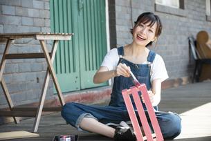 刷毛で箱に色を塗っている女性の写真素材 [FYI04839500]