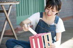 刷毛で箱に色を塗っている女性の写真素材 [FYI04839505]