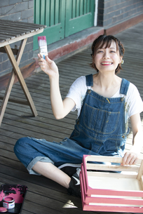 刷毛と手作りの箱を持って笑っている女性の写真素材 [FYI04839509]