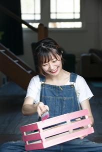 刷毛で箱に色を塗っている女性の写真素材 [FYI04839514]