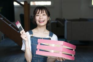 刷毛と手作りの箱を持って笑っている女性の写真素材 [FYI04839517]