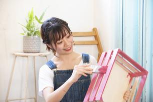 刷毛で箱にペンキを塗っている女性の写真素材 [FYI04839522]