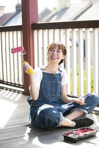 ペイントローラーを持って笑っている女性の写真素材 [FYI04839531]