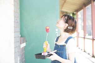 ペイントローラーを持って壁を見上げている女性の写真素材 [FYI04839532]