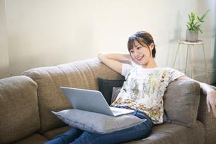 ソファでパソコンの画面を見ている女性の写真素材 [FYI04839564]