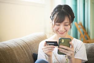 スマホとクレジットカードを持っている女性の写真素材 [FYI04839567]