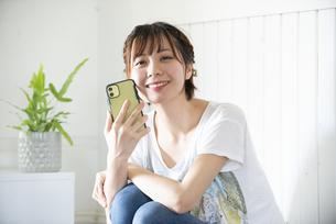 スマホを持って笑っている女性の写真素材 [FYI04839579]