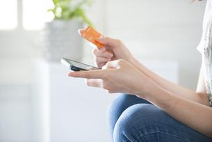 スマホとクレジットカードを持っている女性の手元の写真素材 [FYI04839593]