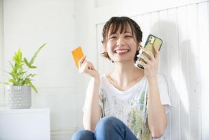 スマホとクレジットカードを持って笑っている女性の写真素材 [FYI04839597]