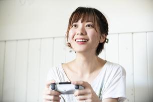 ゲームのコントローラーを持っている女性の写真素材 [FYI04839600]