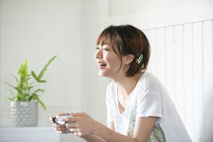ゲームのコントローラーを持っている女性の写真素材 [FYI04839604]