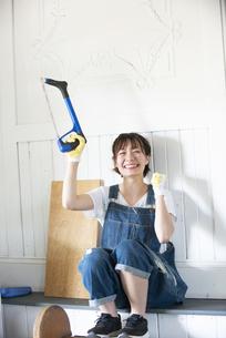 糸ノコを持って笑っている女性の写真素材 [FYI04839645]