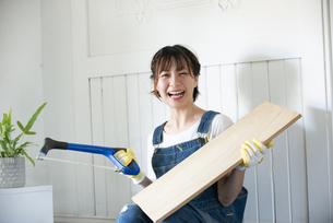 糸ノコと板を持って笑っている女性の写真素材 [FYI04839646]
