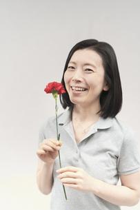 カーネーションを持って笑顔の女性の写真素材 [FYI04839754]