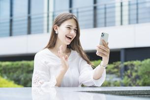スマートフォンを使ってビデオ通話する女性の写真素材 [FYI04839774]