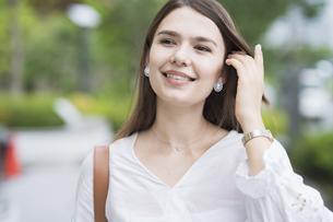 笑顔で、緑あふれる歩道を歩く若いビジネスウーマンの写真素材 [FYI04839811]