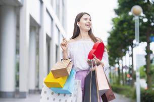 たくさんの買い物袋を抱える女性の写真素材 [FYI04839817]