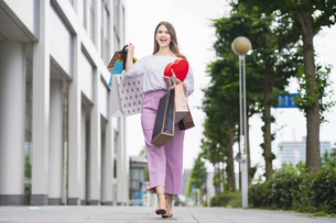 たくさんの買い物袋を抱える女性の写真素材 [FYI04839824]