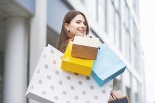 たくさんの買い物袋を抱える女性の写真素材 [FYI04839827]