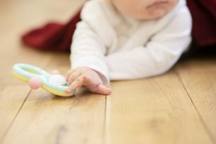FYI04840597  床をハイハイする赤ちゃん(ピントは手前のおもちゃと指先)の写真素材 [FYI04840598]