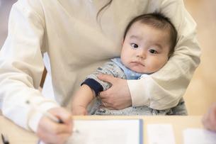 デスクワークをするお母さんに抱かれる赤ちゃんの写真素材 [FYI04840629]