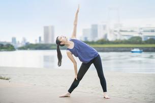 都市のビーチでヨガをする若い女性の写真素材 [FYI04840657]